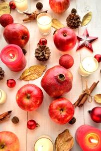 ざくろと林檎とクリスマス飾りとキャンドル 白木材背景の写真素材 [FYI00920458]