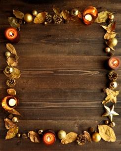 金色の枯葉とクリスマス飾りとキャンドル 黒木材背景の写真素材 [FYI00920472]
