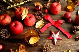 林檎とクリスマス飾りとキャンドル 黒木材背景の写真素材 [FYI00920483]