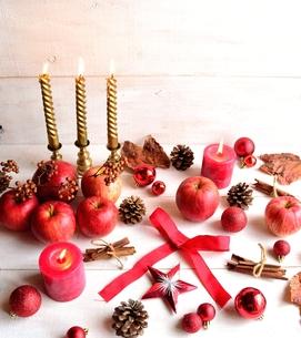 林檎とクリスマス飾りとキャンドル 白木材背景の写真素材 [FYI00920493]