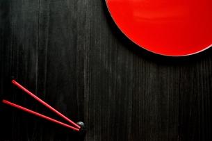 漆塗りのおぼんと赤い箸 黒背景の写真素材 [FYI00920703]