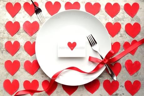 ハートのメッセージカードと白皿とペアのフォーク ハート型の切り絵背景の写真素材 [FYI00921058]