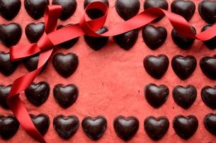 ハート型のチョコレートと赤いリボンのフレーム 赤色背景の写真素材 [FYI00921083]