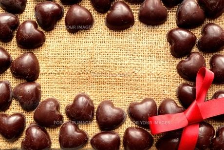 ハート型のチョコレートと赤いリボンのフレーム 麻布背景の写真素材 [FYI00921086]