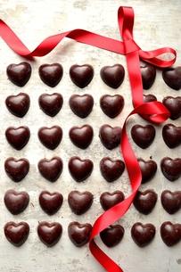 整列したたくさんのハート型のチョコレートとアレンジされた赤いリボンの写真素材 [FYI00921089]