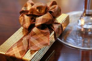 テーブルの上の金色のラッピングとリボンのプレゼントの写真素材 [FYI00921122]