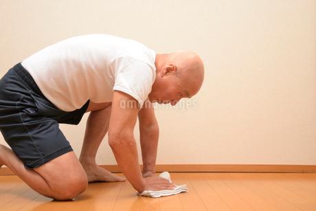 床を拭き掃除をしているシニアの写真素材 [FYI00921192]