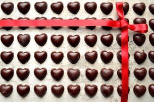 整列したたくさんのハート型のチョコレートと赤いリボンの写真素材 [FYI00921222]