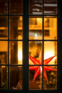 Christmas star and small Christmas tree behind windowpaneの写真素材 [FYI00921307]