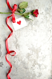 赤い薔薇とハートのメッセージカードと赤いリボンの写真素材 [FYI00921366]