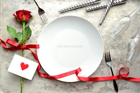 赤い薔薇とハートのメッセージカードと白皿とペアのフォークの写真素材 [FYI00921370]