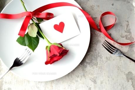 白皿にのせた赤い薔薇とハートのメッセージカードとペアのフォークの写真素材 [FYI00921377]