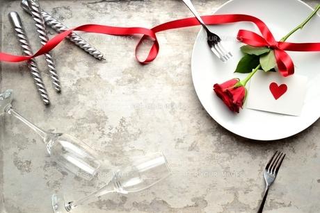 白皿にのせた赤い薔薇とハートのメッセージカードとペアのフォークの写真素材 [FYI00921383]