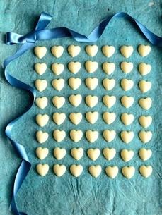 沢山並んだハート型のホワイトチョコレートとリボン 水色背景の写真素材 [FYI00921397]