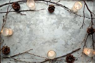 枯枝とまつぼっくりとキャンドルライト フレーム 銀色背景の写真素材 [FYI00921455]