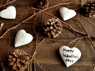 白いハート型オーナメントとまつぼっくり バレンタインデーメッセージ入り 黒木材背景の写真素材 [FYI00921472]