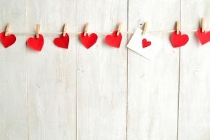 木製のクリップで吊るした赤いハートの切り絵とメッセージカード 白木材背景の写真素材 [FYI00921503]