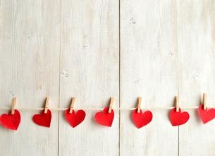 木製のクリップで吊るした赤いハートの切り絵 白木材背景の写真素材 [FYI00921506]