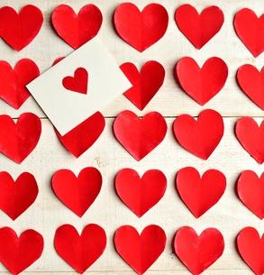 ハートのメッセージカードと整列された赤いハートの切り絵背景の写真素材 [FYI00921514]