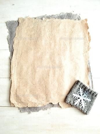 手すき紙と銀色の雪の結晶の切り絵とニット生地の写真素材 [FYI00921550]