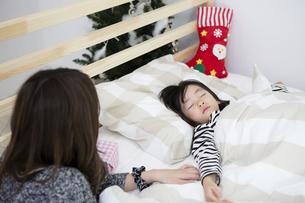 クリスマスの夜に娘を寝かしつける母親の写真素材 [FYI00921692]