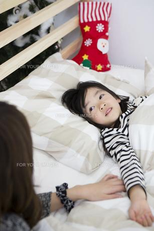 クリスマスの夜に娘を寝かしつける母親の写真素材 [FYI00921693]