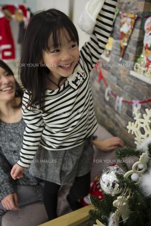 ツリーを飾りつけるお母さんと娘の素材 [FYI00921694]
