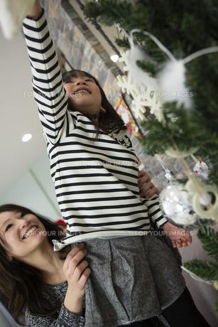 ツリーを飾りつけるお母さんと娘の写真素材 [FYI00921706]