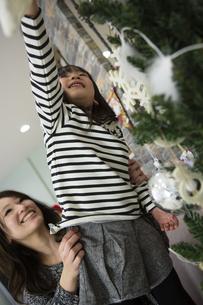 ツリーを飾りつけるお母さんと娘の素材 [FYI00921706]