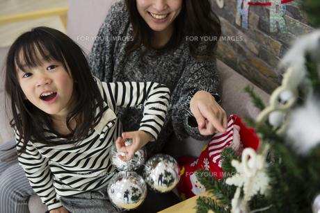 ツリーを飾りつけるお母さんと娘の写真素材 [FYI00921720]