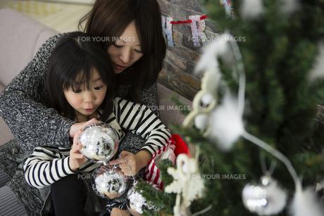 ツリーを飾りつけるお母さんと娘の素材 [FYI00921728]