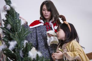ツリーを飾り付けるお母さんと娘の素材 [FYI00921750]