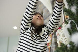 ツリーを飾りつける女の子の素材 [FYI00921751]