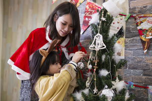 ツリーを飾り付けるお母さんと娘の素材 [FYI00921760]