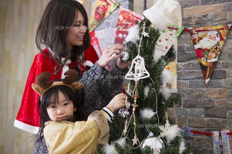ツリーを飾り付けるお母さんと娘の素材 [FYI00921761]