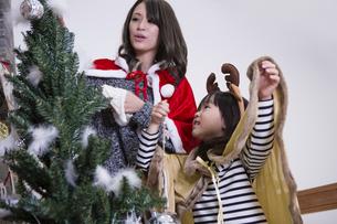 ツリーを飾り付けるお母さんと娘の写真素材 [FYI00921764]