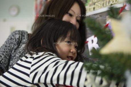 ツリーを飾りつけるお母さんと娘の素材 [FYI00921765]