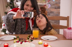 クリスマスに記念撮影をする親子の素材 [FYI00921777]