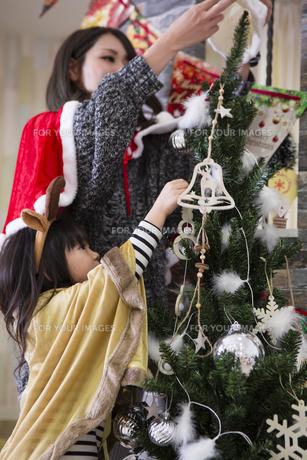 ツリーを飾り付けるお母さんと娘の素材 [FYI00921785]