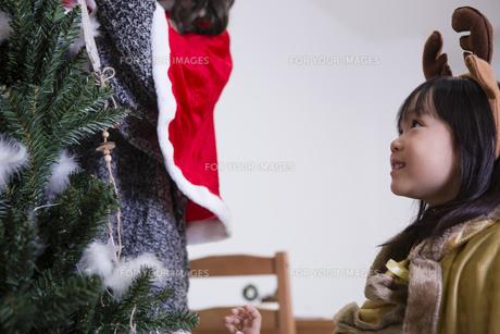 ツリーを飾り付けるお母さんと娘の素材 [FYI00921787]