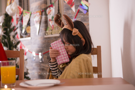 クリスマスプレゼントを抱きしめる女の子の素材 [FYI00921789]