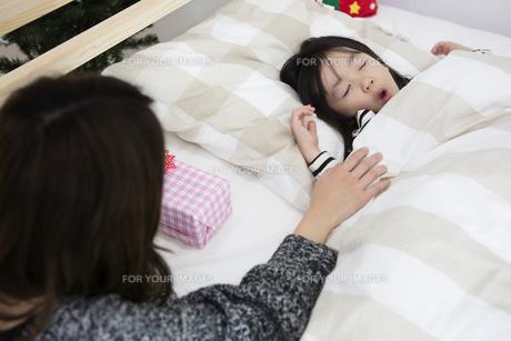 クリスマスの夜に娘を寝かしつける母親の写真素材 [FYI00921792]