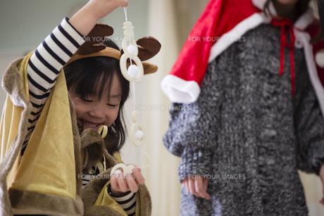 ツリーを飾り付けるお母さんと娘の素材 [FYI00921793]