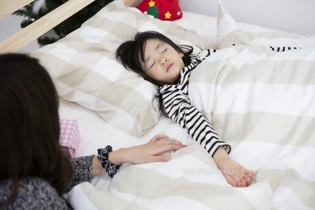 クリスマスの夜に娘を寝かしつける母親の写真素材 [FYI00921795]