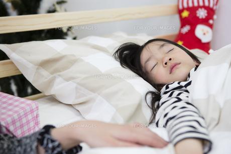 クリスマスの夜に娘を寝かしつける母親の写真素材 [FYI00921796]