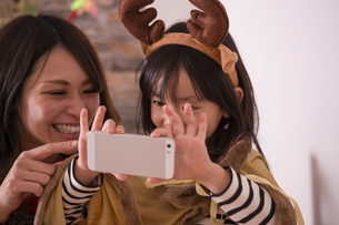 クリスマスに記念撮影をする親子の素材 [FYI00921797]