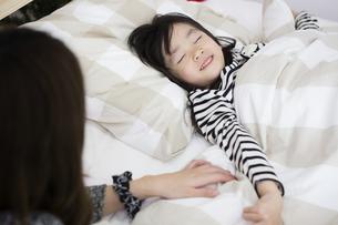 クリスマスの夜に娘を寝かしつける母親の写真素材 [FYI00921809]
