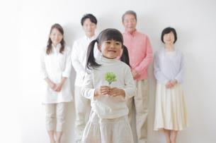 苗を持つ女の子と家族の写真素材 [FYI00922239]