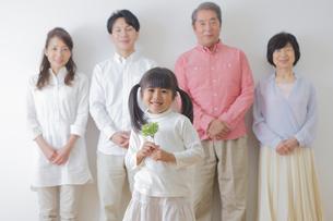 苗を持つ女の子と家族の写真素材 [FYI00922258]