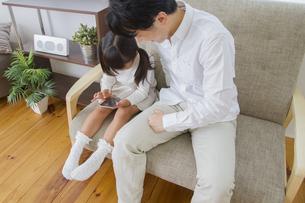 スマホを操作する親子の写真素材 [FYI00922386]